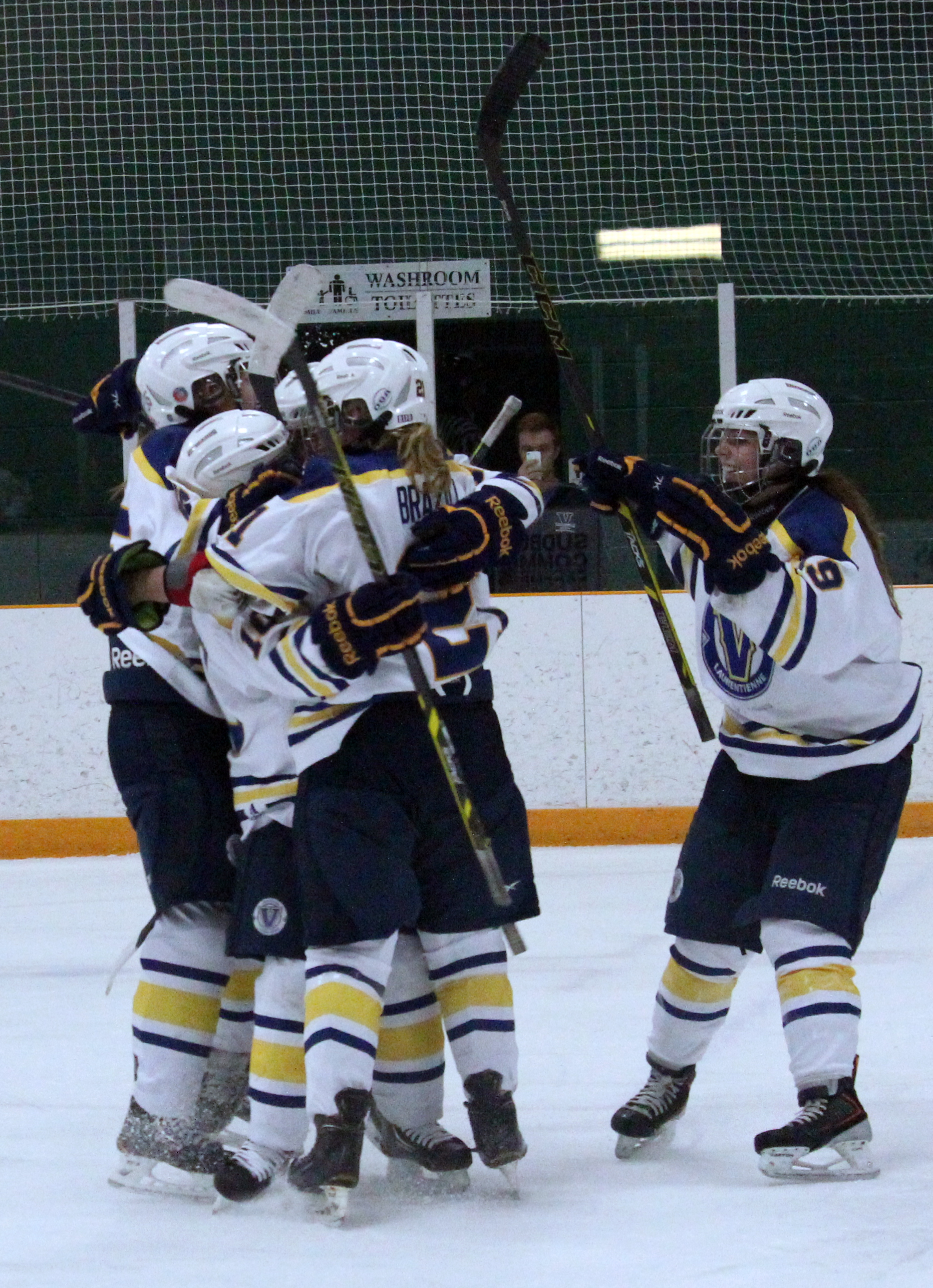 Members of the women's Voyageurs hockey team celebrate after scoring a goal. Photo by Gabriel Rodrigues